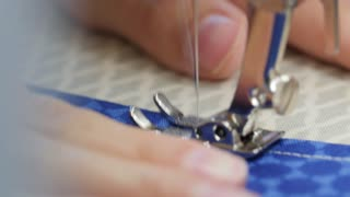 A woman sewing fabric with sewing machine close up