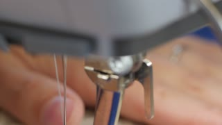 A woman sewing fabric with sewing machine closeup