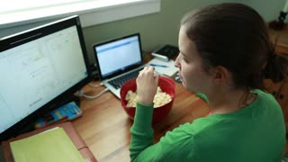 a woman snacking on popcorn in home office