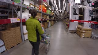 A woman walking through a large warehouse store