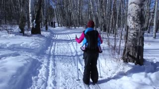 a woman with baby cross country skiing