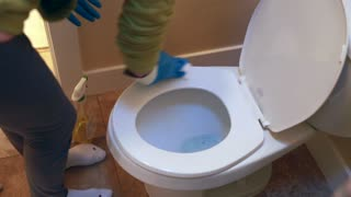 a woman with toddler scrubbing a toilet clean