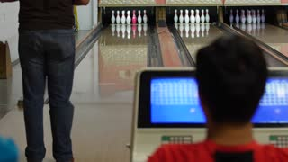 A young family bowls in small town bowling alley