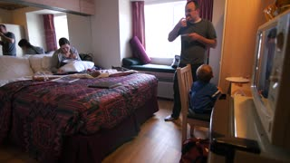 A young family eats pizza in a small hotel room