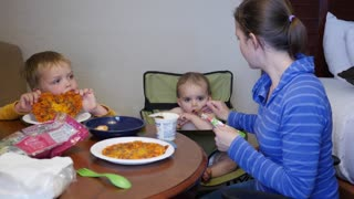 A young family eats their microwave pizzas in hotel room