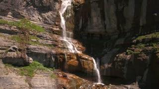 Aerial ascending shot of beautiful mountain waterfall