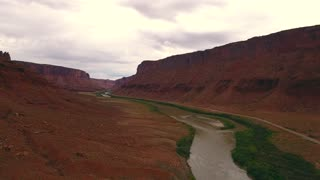 Aerial ascending shot of stormy buttes and river near Moab Utah