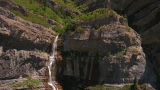 Aerial descending shot of a beautiful mountain waterfall