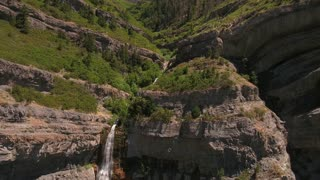 Aerial descending shot of beautiful mountain waterfall in summer