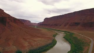 Aerial dolly shot of stormy desert buttes and river near Moab Utah