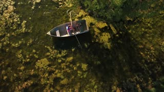 Aerial high shot of two boys rowing  small boat in mossy pond