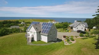 Aerial rotating shot of solar panels on roof of house on ocean coast
