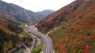 Aerial shot cars on mountain highway with fall colors