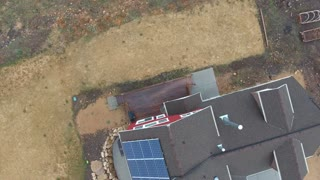 Aerial shot of a home with solar panels on roof in spring