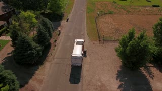 Aerial shot of a local garbage truck lifting the garbage cans