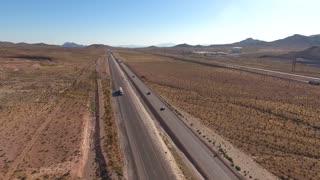 Aerial shot of a long highway in the vast desert