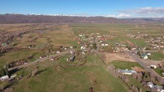 Aerial shot of a rural town and fields in springtime
