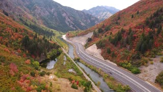 Aerial shot of cars driving on mountain highway with fall colors