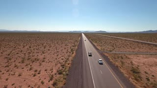 Aerial shot of cars traveling on the long highway in a desert