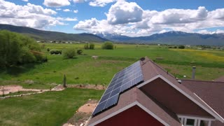 Aerial shot of flying over house with solar panels in spring
