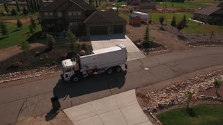 Aerial shot of garbage truck lifting garbage cans