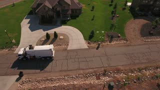 Aerial shot of garbage truck lifting the garbage cans
