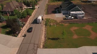Aerial shot of local garbage truck lifting the garbage cans
