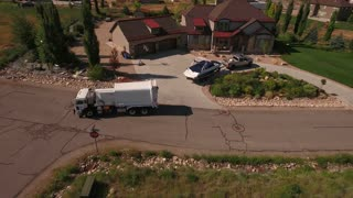 Aerial shot of sanitation truck lifting the garbage cans