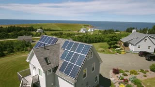 Aerial shot of solar panels on roof of house on ocean coast