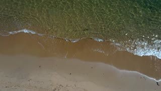 Aerial shot of the calm ocean water on beach