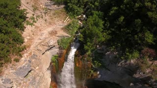 Aerial shot of travelling over the beautiful mountain waterfall