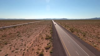 Aerial shot of vehicles traveling on a long highway in a desert