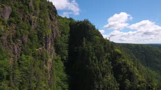 Aerial shot over cliffs and a deep gorge and a mountain forest