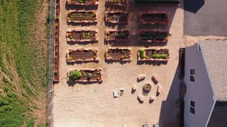 Aerial shot raised garden beds and greenhouse with vegetables