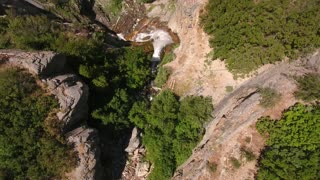 Aerial shot travelling over a beautiful mountain waterfall