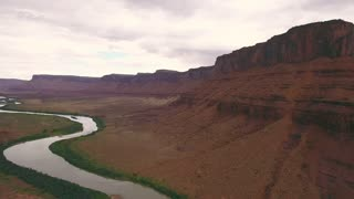 Aerial travelling shot of a stormy buttes and river near Moab Utah