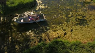 Aerial travelling shot of two boys rowing a small boat in mossy pond