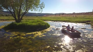 Aerial travelling shot of two boys rowing a small boat in pond