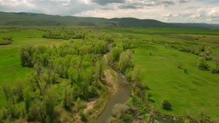 Amazing aerial shot over river in green springtime