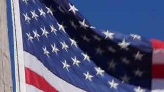 American flag blows in strong wind with blue sky closeup