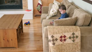 An Adorable Little Boy Toddler Playing An Ipad On The Couch