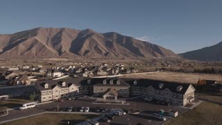 An Aerial Rising Shot Of Retirement Home By The Mountains In City