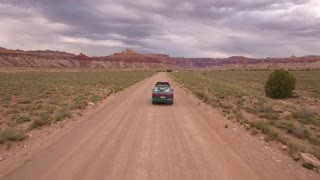 An aerial shot car drives through the desert on a dirt road