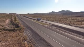 An aerial shot of a long highway in the vast desert