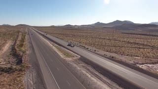 An aerial shot of the long highway in the vast desert