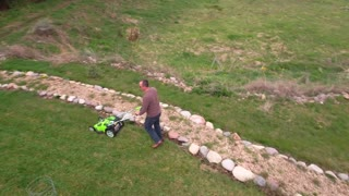 An aerial view of a man mowing his yard lawn
