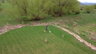 An aerial view of a man mowing the lawn