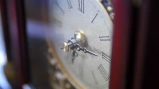 An antique clocks hands turn with time