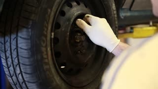 an auto mechanic rotating the tires