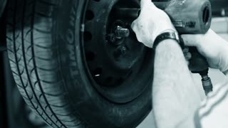 an auto mechanic rotating tires